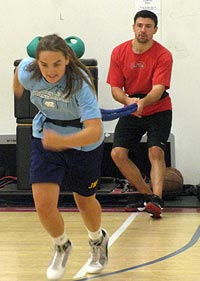 A trainer helping an athlete with a resistance running drill